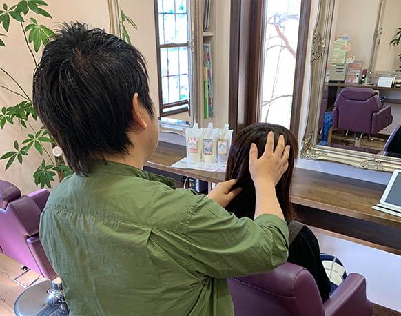 髪質・頭蓋骨の状態をチェックして収まりの良い小顔になるヘアスタイル決め